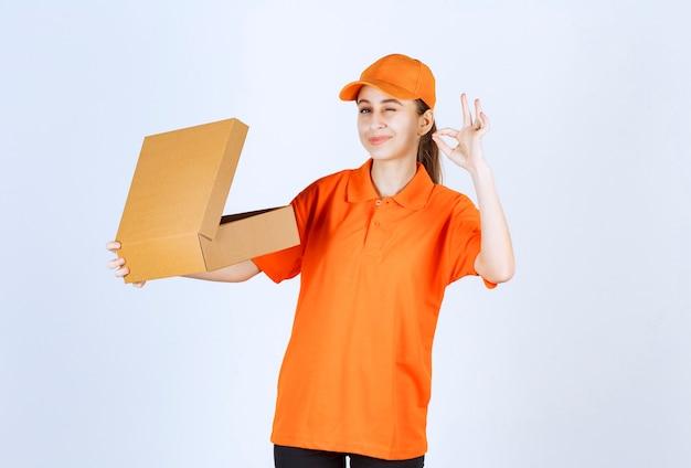 開いた段ボール箱を保持し、肯定的な手のサインを示すオレンジ色の制服を着た女性の宅配便。