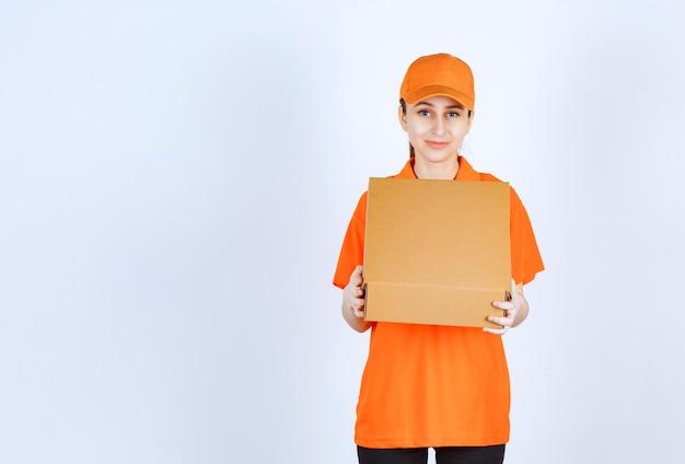 Женский курьер в оранжевой форме держит открытую картонную коробку.