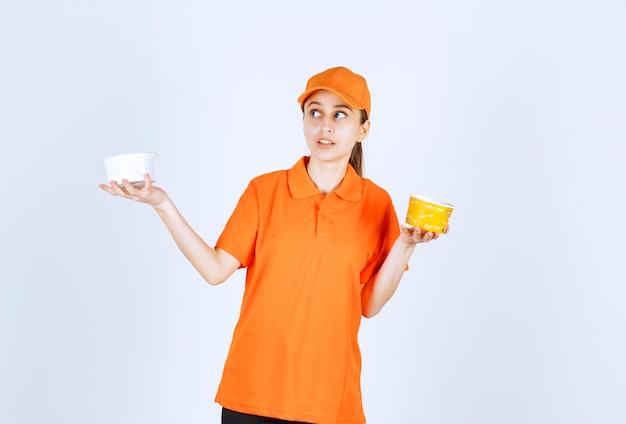 Женский курьер в оранжевой форме держит пластиковую и желтую чашку с лапшой в обеих руках.