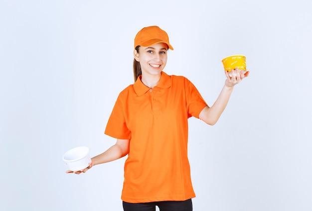 両手にプラスチックと黄色のヌードルカップを保持しているオレンジ色の制服を着た女性の宅配便
