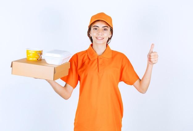 黄色と白のテイクアウトボックスを保持しているオレンジ色の制服を着た女性の宅配便