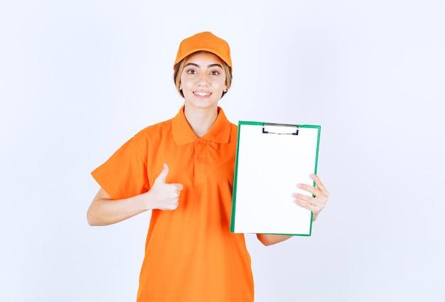 顧客リストを示し、満足のサインを示すオレンジ色の制服を着た女性の宅配便