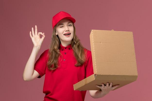 ピンクの制服サービス提供労働者のフードボックスを保持し、開く赤い制服の女性宅配便