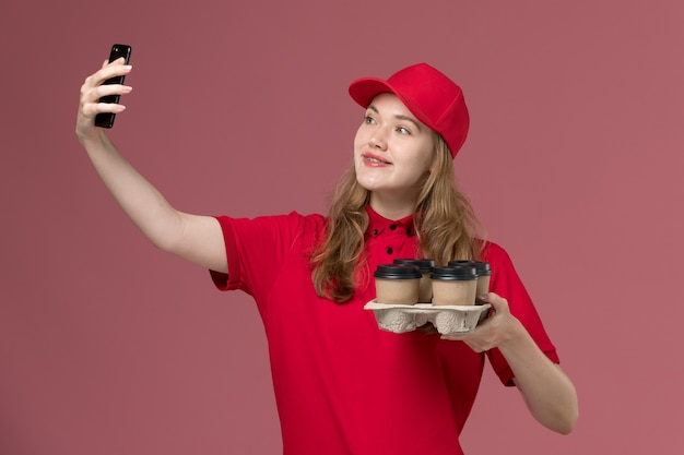 Женщина-курьер в красной форме с коричневыми кофейными чашками делает селфи на розовой, униформе работника службы доставки
