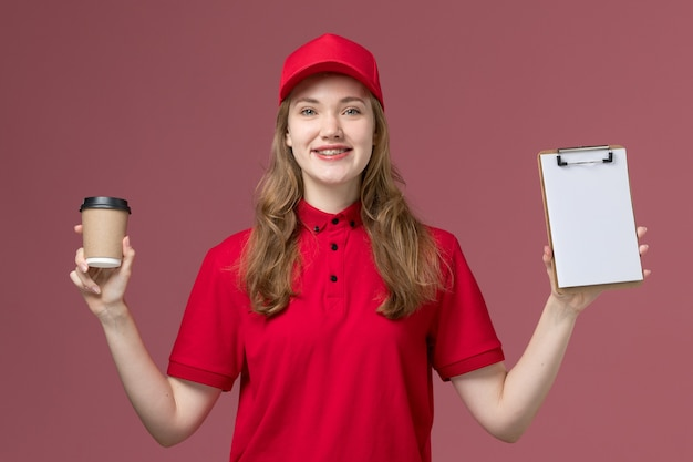 ピンクの笑顔で茶色の配達コーヒーとメモ帳を保持している赤い制服の女性の宅配便、仕事の制服労働者サービス