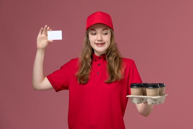 ピンクの、均一なサービス提供労働者に茶色の配達コーヒーカップとカードを保持している赤い制服の女性宅配便