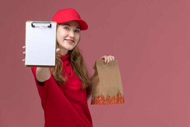 분홍색, 균일 한 직업 노동자 서비스 배달에 메모장으로 갈색 음식 패키지를 들고 빨간 제복을 입은 여성 택배