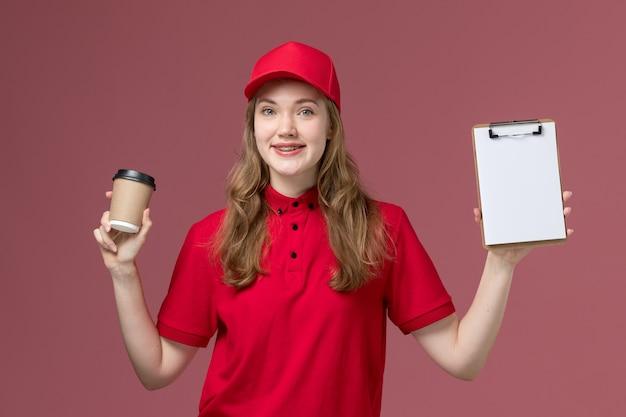 Женщина-курьер в красной униформе держит чашку кофе и блокнот на розовом, униформенном работнике службы доставки