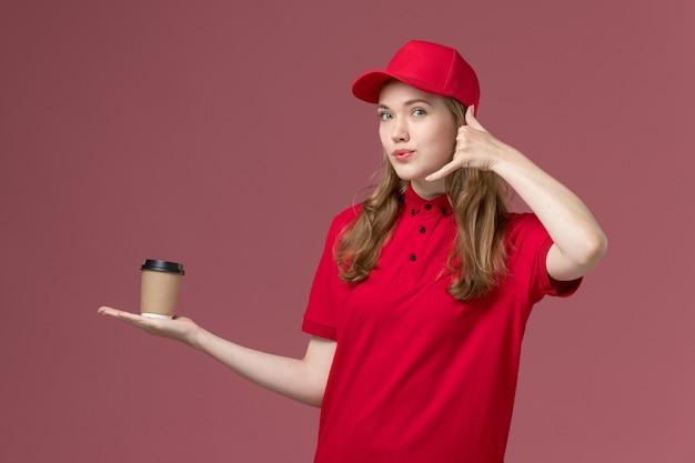 淡いピンクの、仕事の制服のサービスワーカーの配達でポーズをとってコーヒーカップの電話を保持している赤い制服を着た女性の宅配便