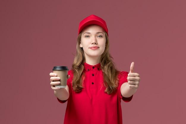 淡いピンクでポーズをとってコーヒーカップを保持している赤い制服を着た女性の宅配便、仕事の制服サービスワーカーの配達