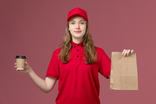 ピンクの制服サービス提供の仕事で食品パッケージとコーヒーカップを保持している赤い制服の女性の宅配便