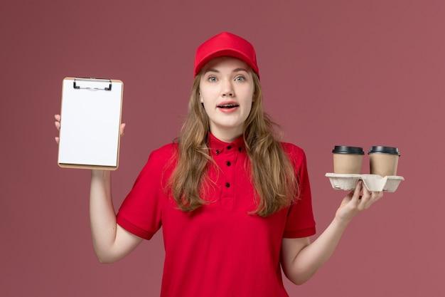 ピンクの均一なサービス提供の仕事でコーヒーカップとメモ帳を保持している赤い制服を着た女性の宅配便