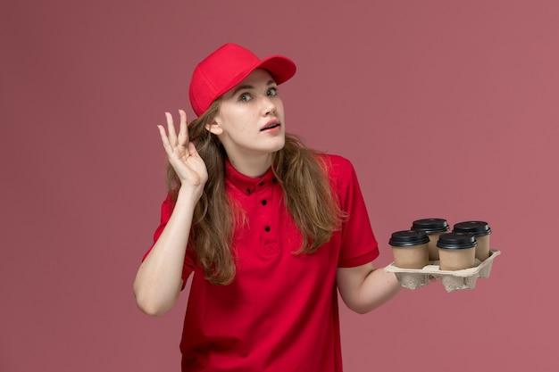 Женщина-курьер в красной форме держит кофейные чашки, пытаясь выслушать розовую, униформу служащего службы доставки