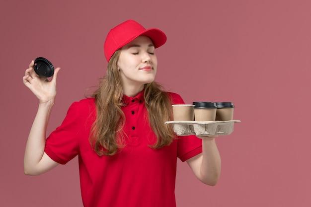 Женщина-курьер в красной форме держит доставку кофейных чашек, нюхает их на розовом, рабочая форма службы доставки
