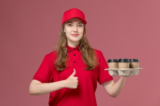 Женщина-курьер в красной форме держит доставку кофейных чашек, улыбаясь на светло-розовом, рабочая форма службы доставки