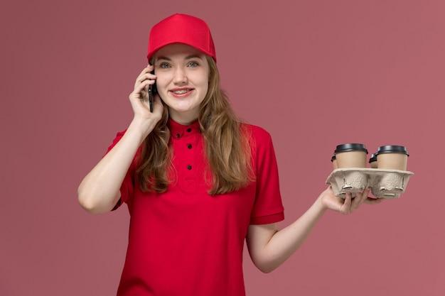 ピンクの笑顔で電話で話している配達コーヒーを保持している赤い制服を着た女性の宅配便、仕事の制服労働者サービスの配達