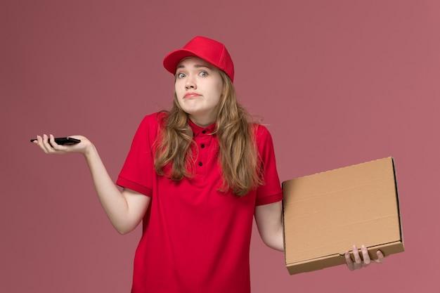Женщина-курьер в красной форме держит коробку для доставки еды и телефон на светло-розовом, униформе работник службы доставки девушка