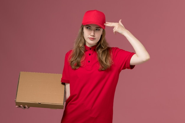 ピンクの制服のサービス提供の仕事の労働者を考えて食品配達ボックスを保持している赤い制服の女性の宅配便