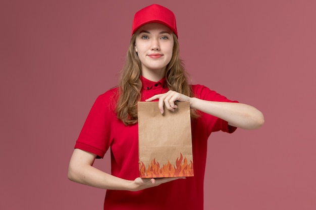 ライトピンクの食品パッケージを保持している赤い制服を着た女性の宅配便、仕事の制服のサービスワーカーの配達