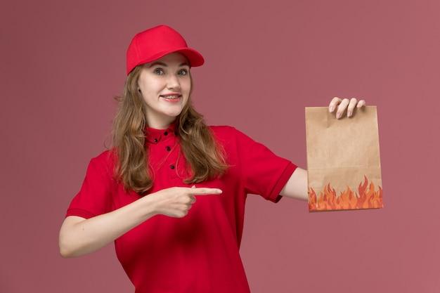 ピンクの笑顔とポーズで食品パッケージを保持している赤い制服を着た女性の宅配便、仕事の制服労働者サービスの提供