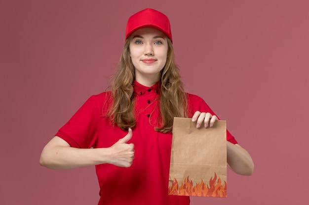 ピンクの制服のジョブワーカーサービスの配信で食品紙パッケージを保持している赤い制服の女性の宅配便