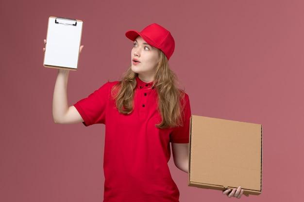 Женщина-курьер в красной форме держит блокнот и коробку с едой на светло-розовом, рабочая форма службы доставки