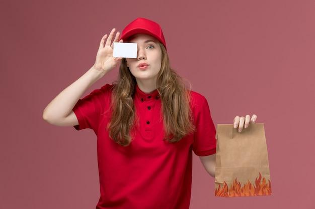 Женщина-курьер в красной форме держит бумажный пакет с едой и белую карточку на светло-розовом, рабочая форма служба доставки работника