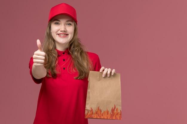 Женщина-курьер в красной форме держит бумажный пакет с едой на светло-розовом, рабочая форма доставки службы