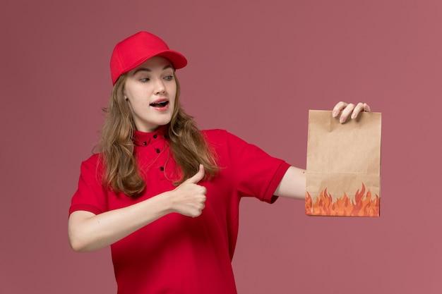 Женщина-курьер в красной форме держит бумажный пакет с едой на розовом, униформе работника службы доставки