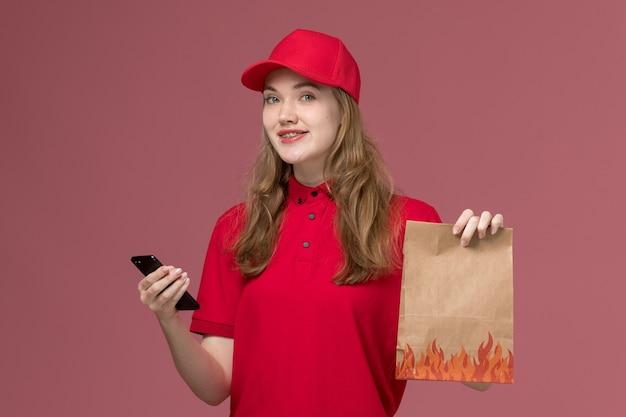 Женщина-курьер в красной форме держит бумажный пакет продуктов с телефоном на светло-розовом, рабочая форма работник службы доставки