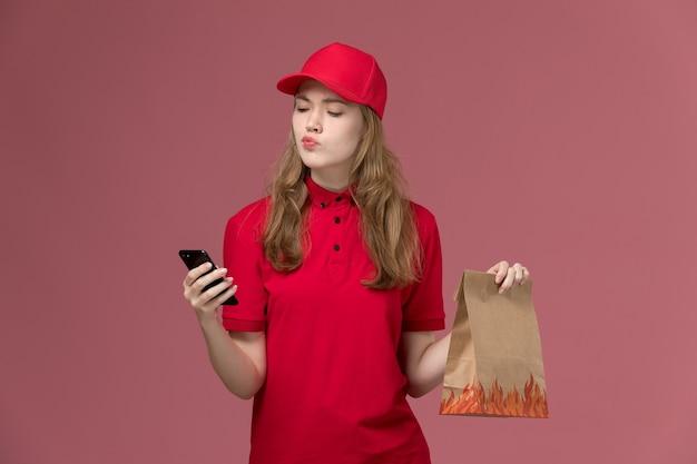 淡いピンクのジョブユニフォームサービスワーカーの配達で電話と食品パッケージを保持している赤い制服の女性の宅配便