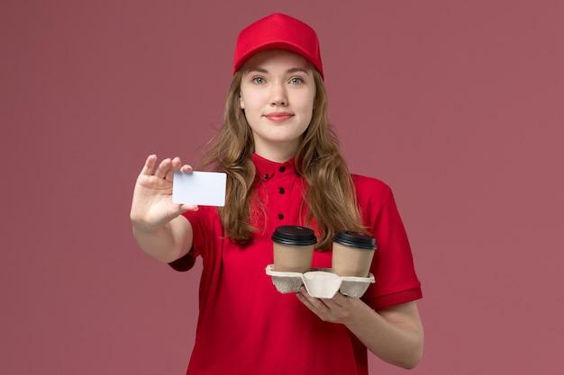 ピンクの制服サービスに笑顔で白いカードとコーヒーカップを保持している赤い制服を着た女性の宅配便