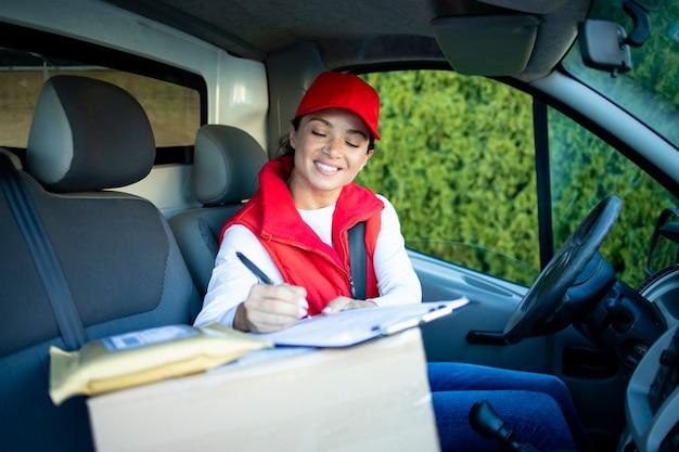 Женский курьер в фургоне проверяет документы перед доставкой груза.