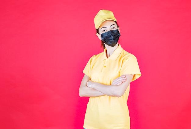 노란색 제복을 입은 여성 택배와 검은색 마스크가 팔짱을 끼고 자신감이 있어 보입니다.