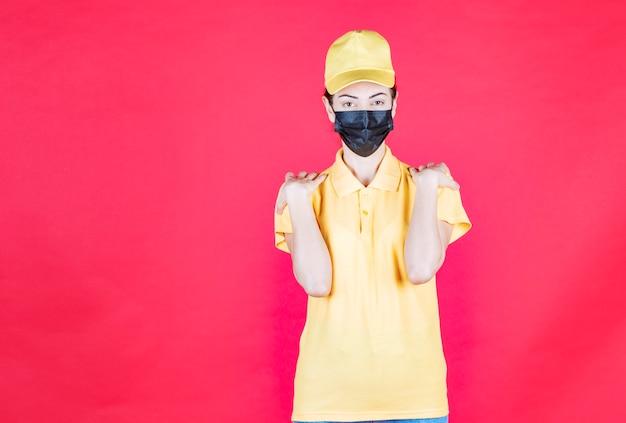 그녀의 주먹을 보여주는 노란색 유니폼과 검은 마스크에 여성 택배