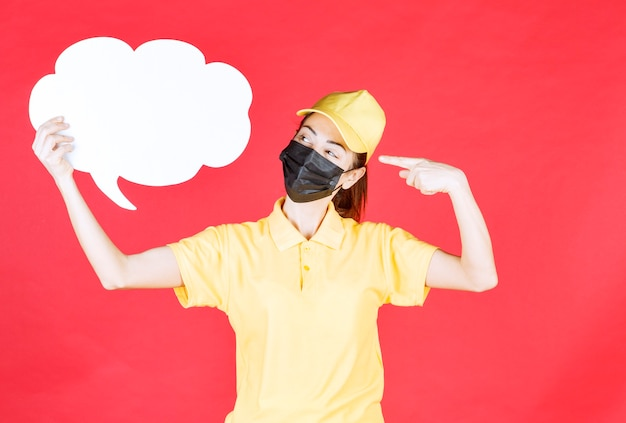 雲の形の情報ボードを保持し、それを指している黄色の制服と黒のマスクの女性の宅配便