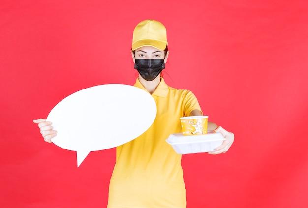 Курьер-женщина в желтой форме и черной маске держит чашку с лапшой, упаковку на вынос и информационное табло