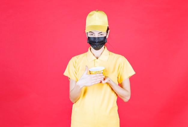 Женский курьер в желтой форме и черной маске держит чашку с лапшой