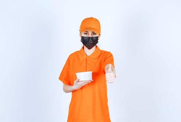 Женский курьер в желтой форме и черной маске держит пластиковый стаканчик и показывает знак рукой.