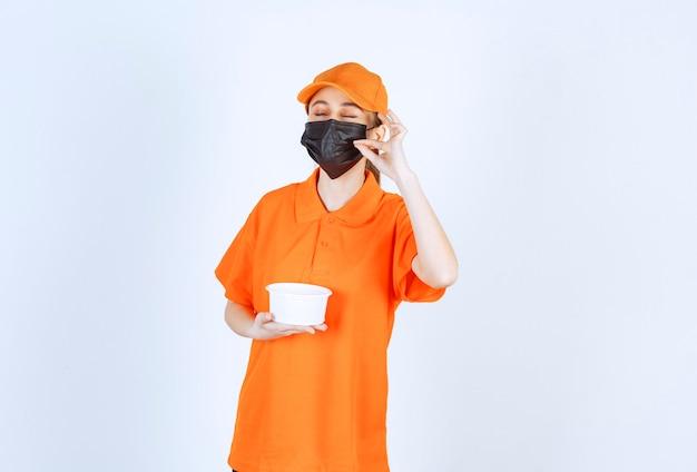 プラスチック製のコップを保持し、肯定的な手のサインを示す黄色の制服と黒のマスクの女性の宅配便