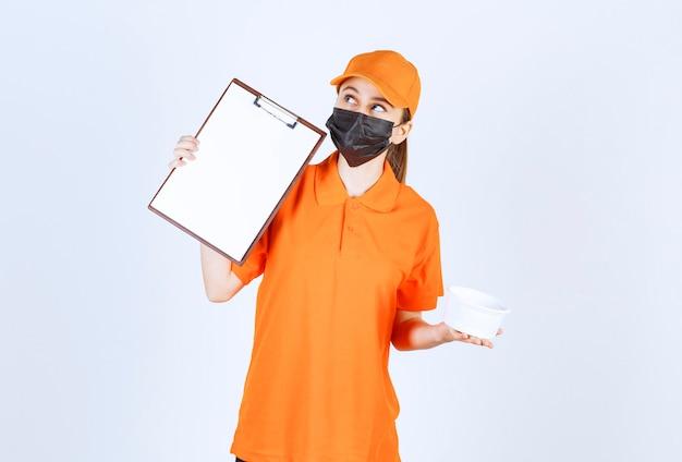 노란색 제복을 입은 여성 택배와 플라스틱 테이크아웃 식품 상자와 서명 목록을 들고 있는 검은색 마스크