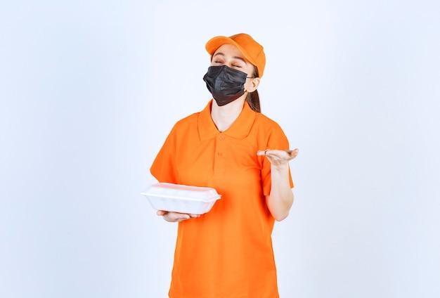 Курьер-женщина в желтой форме и черной маске держит пластиковую коробку для еды на вынос и нюхает вкус.