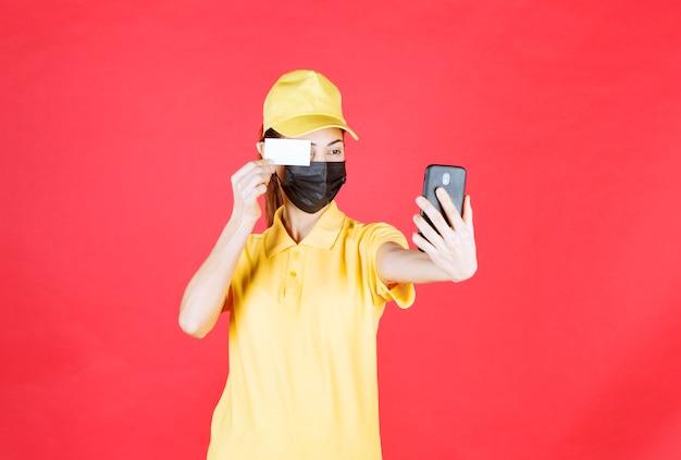 Женский курьер в желтой форме и черной маске держит смартфон и делает селфи, показывая свою визитную карточку