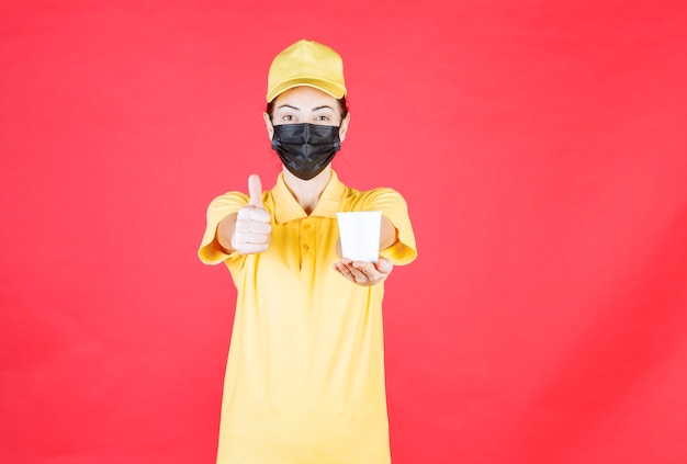 テイクアウトカップを持って味を楽しむ黄色い制服と黒いマスクの女性宅配便