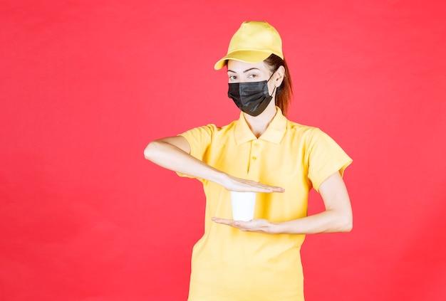 テイクアウトカップを保持している黄色の制服と黒のマスクの女性の宅配便