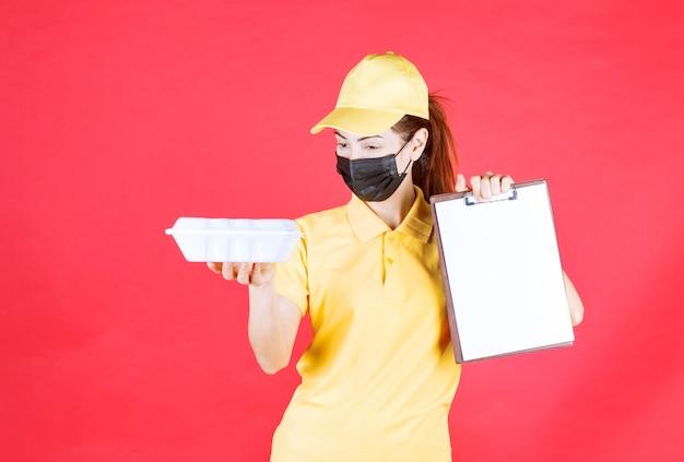 노란색 유니폼과 검은색 마스크를 쓴 여성 택배기사가 테이크아웃 패키지를 들고 서명 목록을 제시합니다.