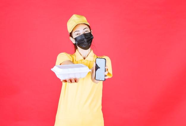 Женский курьер в желтой форме и черной маске держит посылку на вынос и принимает заказы через смартфон