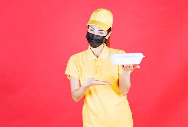 노란색 제복을 입은 여성 택배와 테이크아웃 패키지를 들고 있는 검은색 마스크