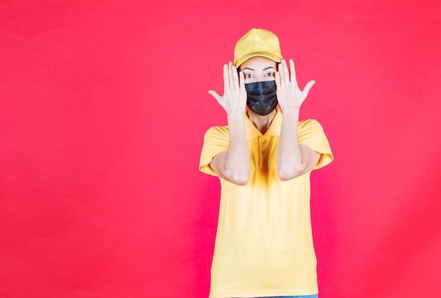彼女の顔を保持し、怖いと恐怖に見える黄色の制服と黒のマスクの女性の宅配便