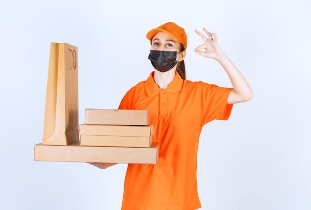Женский курьер в желтой форме и черной маске держит несколько картонных пакетов и хозяйственную сумку и показывает положительный знак рукой.